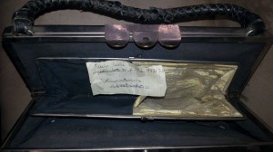 Ikivanha käsilaukku, jonka sisällä osoite Argadiankatu [sic!] ja nelinumeroinen puhelinnumero.